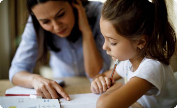 Professeur aide une jeune élève à comprendre son devoir