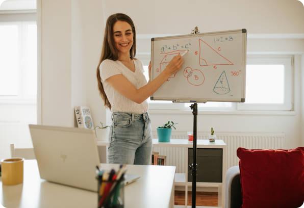 professeur donne un cours en visio et explique les formules sur le tableau